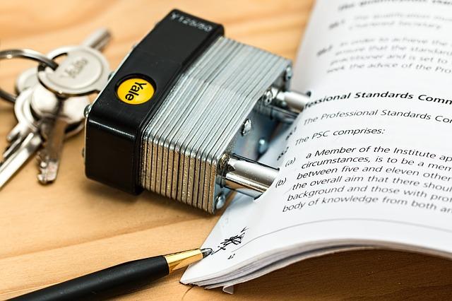 """dokumenty """"uzamčené"""" zámkem na dřevěném stole"""